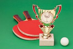 Sports awards and  tennis racquets. On a green table Stock Image