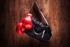 Sports bag and boxing gloves hanging on a wall Stock Photo