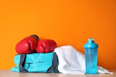 Sports bag, boxing gloves, towel and bottle. Of water on wooden table against color background royalty free stock photos