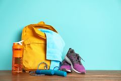 Sports bag and gym equipment. On wooden floor against color background stock image