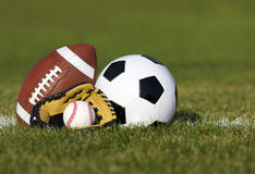 Sports balls on the field with yard line. Soccer ball, American football and Baseball in yellow glove on green grass Royalty Free Stock Photos
