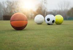 Sports balls on grass field. Various sports balls on grass field Stock Photos