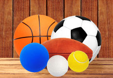 Sports balls on wooden table over wooden planks background Stock Photo