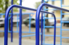 Sports bars in blue on the background of a street sports ground for training in athletics. Outdoor athletic gym equipment. Macro. Photo with selective focus and royalty free stock images