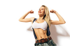 Sports beautiful blonde girl showing biceps and smiling Royalty Free Stock Photography