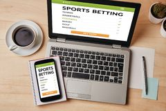 Sports betting concept on laptop and smartphone screen. Over wooden table. All screen content is designed by me. Flat lay stock photos