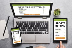 Sports betting concept on laptop, tablet and smartphone screen. Over gray table. All screen content is designed by me. Flat lay royalty free stock images