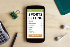 Sports betting concept on smart phone screen on wooden desk. All screen content is designed by me. Flat lay royalty free stock photos