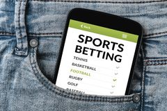 Sports betting concept on smartphone screen in jeans pocket. All screen content is designed by me. Flat lay stock photo