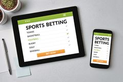 Sports betting concept on tablet and smartphone screen. Over gray table. All screen content is designed by me. Flat lay stock photography