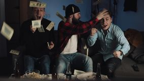 Sports betting. Three friends celebrating success for their favorite football team at home. Dollar bills falling down