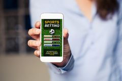 Sports betting app in a mobile phone screen. Sports betting website in a mobile phone screen while woman holds the device stock image