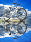 Sports bike against the sky reflected in the water Royalty Free Stock Photography
