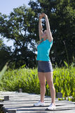 Sports blond girl stretching her arms for body energy, outdoors Stock Photo
