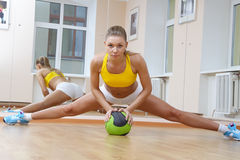 Sports blonde girl do the splits in gym. Beautiful Girl in Fitness Gym Photoshoot. More images of this models you can find in my portfolio Stock Image