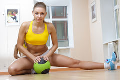 Sports blonde girl do the splits in gym. Beautiful Girl in Fitness Gym Photoshoot. More images of this models you can find in my portfolio Royalty Free Stock Images
