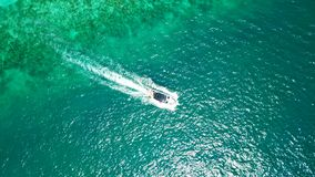 Sports boat in the blue sea. The view from the drone. Expensive vacation. Yacht and turquoise, clear water. Transparent bottom of the water. Visible coral and stock photography