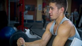 One Sports bodybuilder young man hard training biceps muscles in gym stock footage