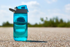 A sports bottle with water stands on the road. Concept of sport and refreshment Stock Photos