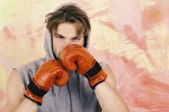 Sports, box and fight concept. Boxer with concentrated face trains. Man with messy hair. On colorful background, copy space. Guy in grey sleeveless hoodie wears stock photo