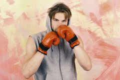 Sports, box and fight concept. Boxer with concentrated face trains to punch. Guy in grey sleeveless hoodie wears red leather boxing gloves. Man with messy hair stock photo