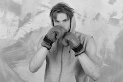 Sports, box and fight concept. Boxer with concentrated face trains to punch. Guy in grey sleeveless hoodie wears red leather boxing gloves. Man with messy hair stock photos