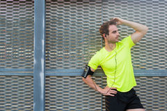 Sports build male taking break after an intense workout while standing against silver wall with copy space area for content Stock Photography