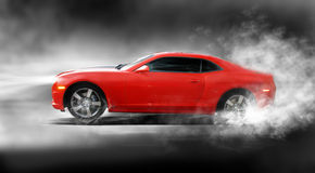 Sports car. A red camaro sports car accelerating with smoke coming from wheels Stock Photos