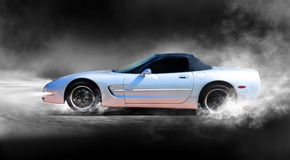 Sports car. A silver corvette sports car accelerating with smoke coming from wheels Stock Photos