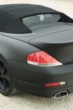 Sports Car. The rear side of a matt black sports car Royalty Free Stock Photo