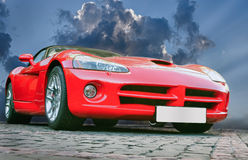 Sports car. Red sports powerful car on stone blocks against  sky Stock Photography