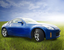 Sports car. A bright blue sports car sitting in a field of grass under a cloudy sky