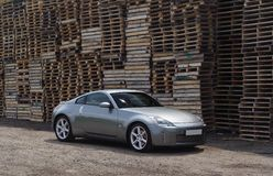 Sports car. Modern sports car in front of piles of cargo pallets royalty free stock image