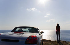 Sports car. Back view of a sports car. Woman standing in front. Beautiful sea view from the edge of the road Royalty Free Stock Photography
