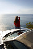 Sports car. View of a sports car. Woman standing in front. Beautiful sea view from the edge of the road Royalty Free Stock Photos