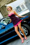 Sports Car Blonde. Blonde fashion model in sexy dress standing next to a black sports car Stock Photo