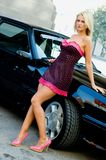 Sports Car Blonde. Blonde fashion model in sexy dress standing next to a black sports car Royalty Free Stock Photos