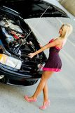 Sports Car Blonde. Blonde fashion model in sexy dress checking out the engine in a black sports car Royalty Free Stock Image