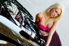 Sports Car Blonde. Blonde fashion model in sexy dress checking out the engine in a black sports car Stock Photos
