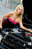 Sports Car Blonde. Blonde fashion model in sexy dress checking out the engine in a black sports car Stock Photo