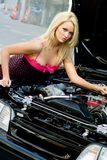 Sports Car Blonde. Blonde fashion model in sexy dress checking out the engine in a black sports car Stock Photography