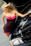 Sports Car Blonde. Blonde fashion model in sexy dress checking out the engine in a black sports car Stock Image