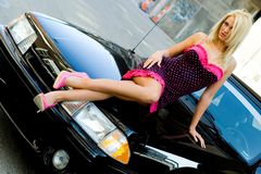 Sports Car Blonde. Blonde fashion model in sexy dress laying on a black sports car Royalty Free Stock Images