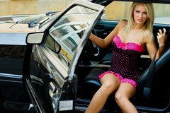 Sports Car Blonde. Blonde fashion model in sexy dress getting out of a black sports car Royalty Free Stock Photos