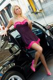 Sports Car Blonde. Blonde fashion model in sexy dress standing next to a black sports car Stock Images