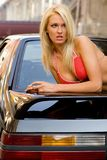 Sports Car Blonde. Sexy blonde fashion model in a swim suit laying on a black sports car Royalty Free Stock Photos