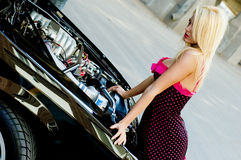 Sports Car Blonde. Blonde fashion model in sexy dress checking out the engine in a black sports car Royalty Free Stock Photos
