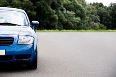 Sports car blue. Sports car - modern blue coupe on road, focus on headlight with ample copyspace Royalty Free Stock Photography