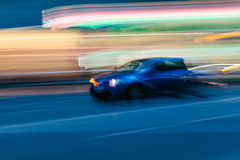 Sports Car in a Blurred City Scene Stock Images