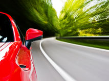 Sports car driving. Motion blur shot of a car driving in a curve royalty free stock photography